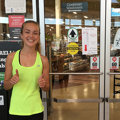 Emma Moore next to GoHere Decal at Sobeys