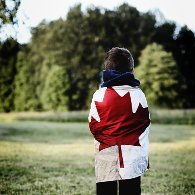 Young boy wrapped in Canadian flag